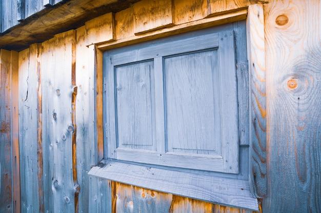 Janela fechada muito pequena em uma bela parede de madeira de uma casa antiga