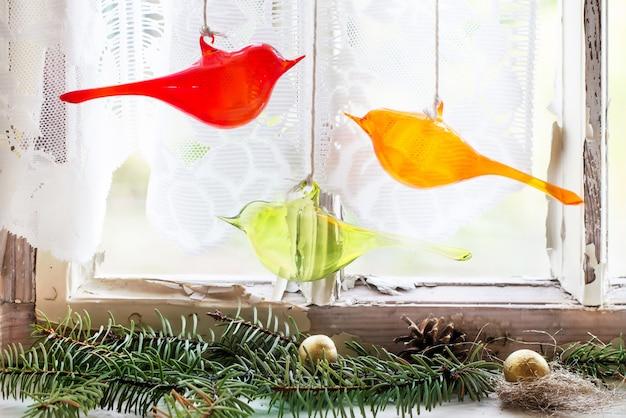 Janela interior com pássaros de vidro e árvore de natal