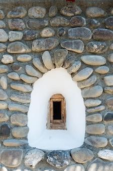 Janela na fachada de um muro de pedra
