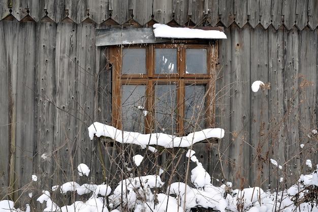 Janela na parede de uma velha casa de madeira. fragmento de um velho,
