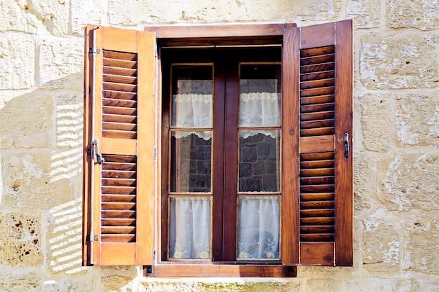 Janela tradicional com persianas de madeira