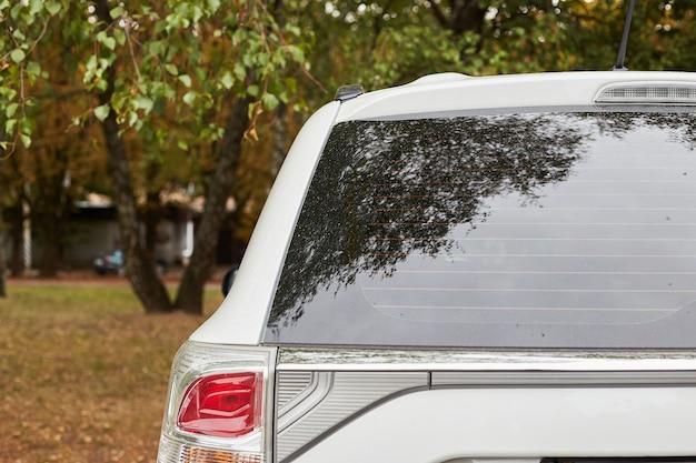 Janela traseira do carro branco estacionado na rua em um dia ensolarado de verão, vista traseira. mock-up para adesivo ou decalques