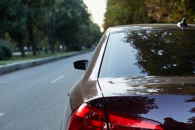 Janela traseira do carro marrom estacionado na rua.