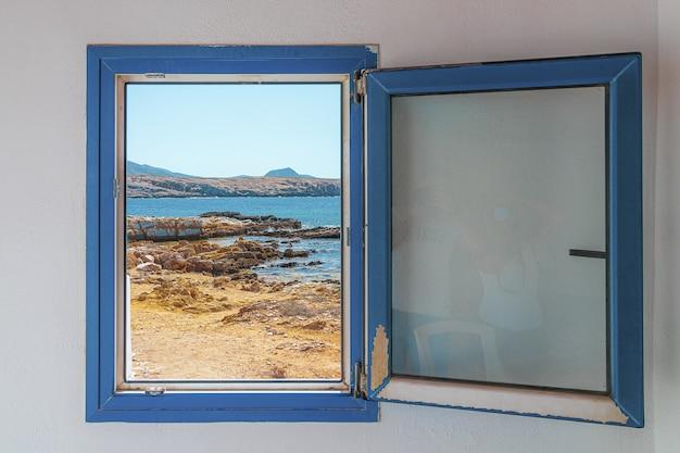 Janela velha de madeira azul com vista para a praia
