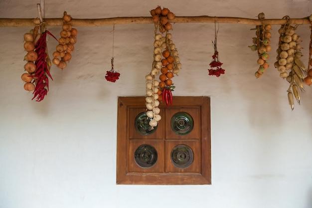 Janela velha, verduras secas e frutas vermelhas penduradas em corda, velha casa de pescador em mamaevo sloboda