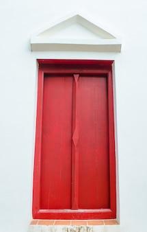 Janela vermelha na parede branca com empena no templo