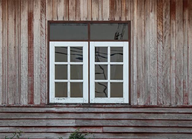Janelas brancas da cor e parede de madeira marrom velha.
