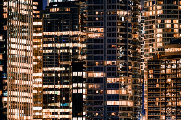 Janelas da fachada do arranha-céu moderno iluminado com prédio de escritórios