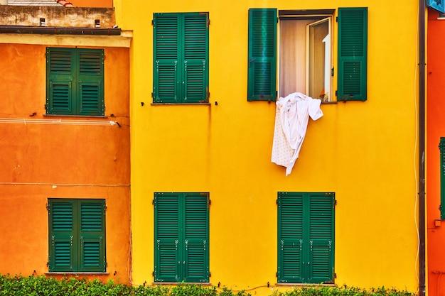 Janelas de casas coloridas em amarelo-laranja e roupas de cama na rua, gênova, itália