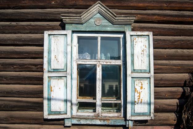 Janelas de madeira com padrões esculpidos nas janelas em uma casa de madeira rústica