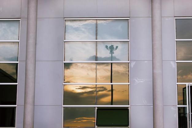 Janelas de vidro refletem a sombra do céu.
