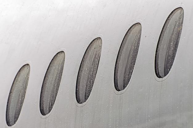 Janelas de vigia de um tempo úmido de avião em gotas de chuva de água, close-up.