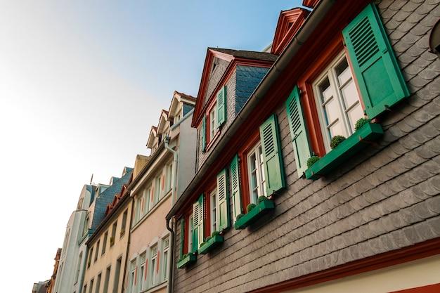 Janelas europeias com persianas de madeira verdes em casa velha