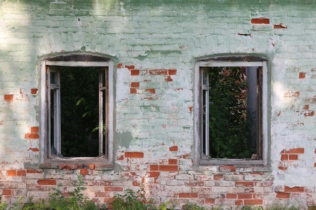 Janelas quebradas de uma casa de tijolos abandonada