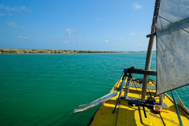 Jangada amarela em piscinas naturais na praia de muro alto em porto de galinhas próximo ao recife pernambuco