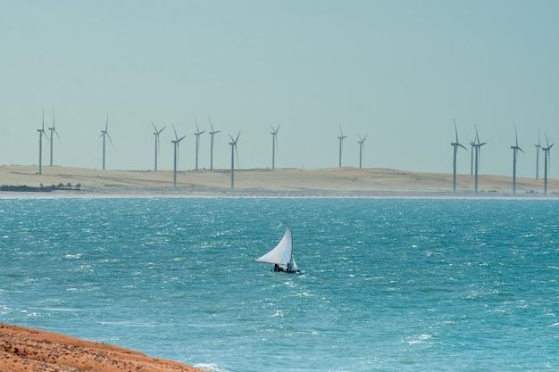 Jangada no mar e turbinas eólicas em aracati perto de fortaleza ceará brasil