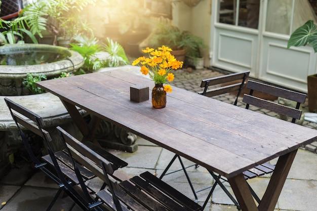 Jantando a tabela de madeira no jardim exterior decorado com os vasos de flor amarelos.