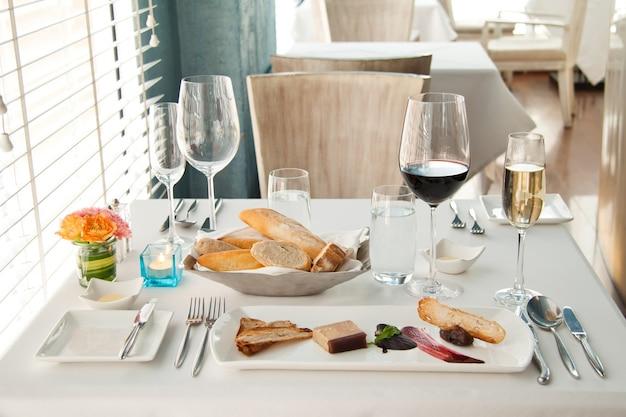 Jantar ajustado na mesa branca, conjunto luxuoso completo de jantar francês