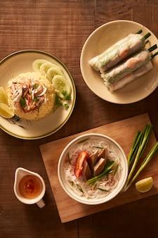 Jantar asiático variado, comida vietnamita. arroz de frango, pão cha ca, macarrão, rolinhos primavera