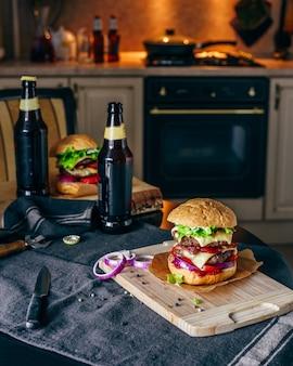 Jantar com dois hambúrgueres de hambúrguer e uma garrafa de cerveja na mesa da cozinha