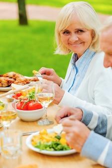 Jantar com o mais próximo. casal sênior comendo e sorrindo enquanto está sentado à mesa de jantar ao ar livre