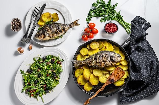 Jantar com pargo grelhado, salada de rúcula com tomate e batatas assadas. fundo branco. vista do topo
