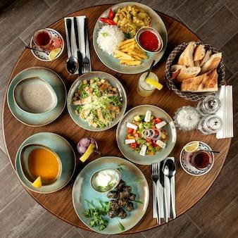 Jantar com sopas de dolma, saladas e frango com arroz e batata frita