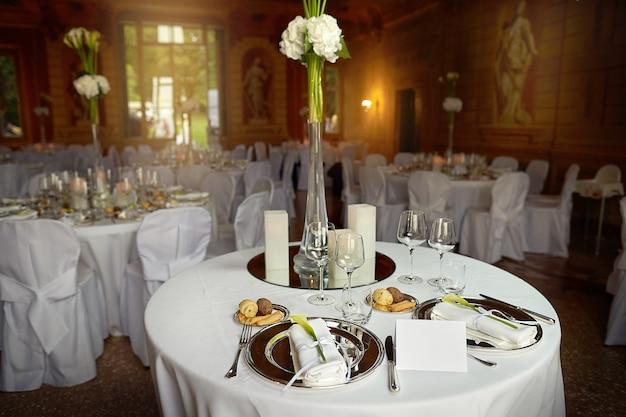 Jantar comemorativo em um restaurante decorado com decorações florais e paredes em estilo deco