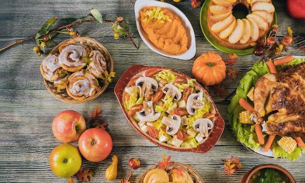 Jantar de ação de graças servido com peru, decorado com folhas de outono e abóbora.