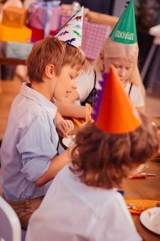 Jantar de aniversário. adolescente alegre a abaixar a cabeça enquanto vai comer pizza