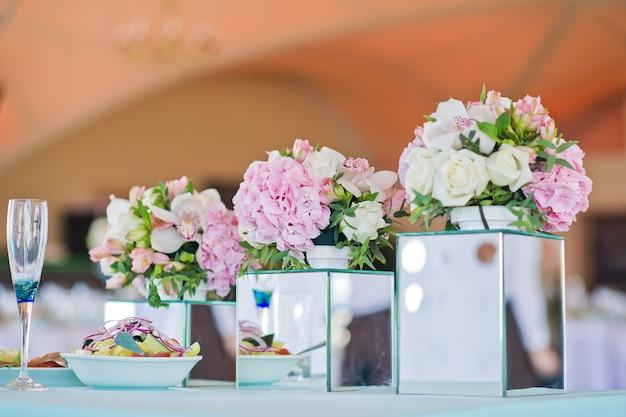 Jantar de casamento no restaurante, mesas decoradas com vasos de rosas.