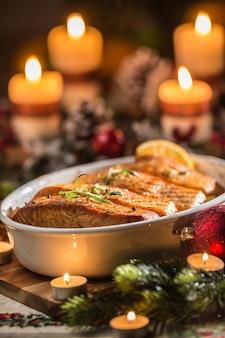 Jantar de natal de peixe salmão em assadeira com coroa do advento de decoração festiva e velas acesas.