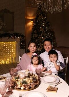 Jantar de natal feliz, família asiática com crianças sorrindo junto à lareira e árvore de natal