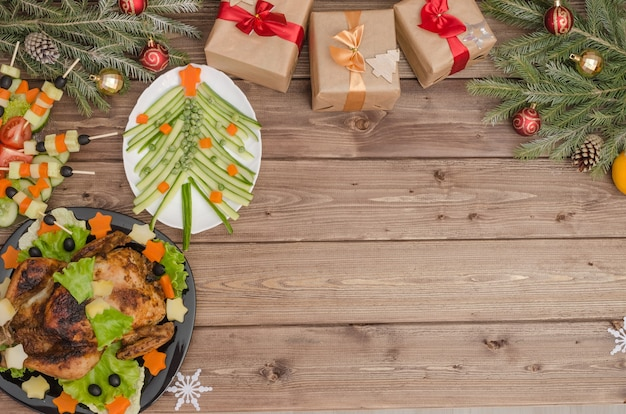 Jantar de natal - frango assado, árvore e canapés de legumes em uma mesa de madeira com espaço de cópia, a ideia de um belo cenário
