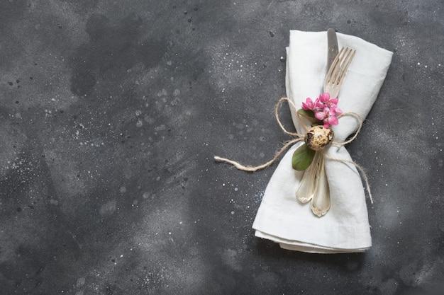 Jantar de páscoa. tabela de elegância, definindo flores cor de rosa no escuro.