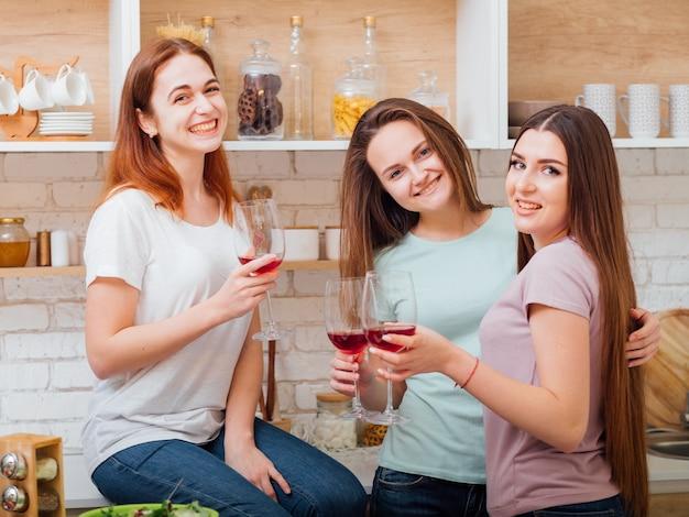 Jantar em casa. diversão de celebração de aniversário. melhores amigos bebendo vinho tinto e se divertindo.