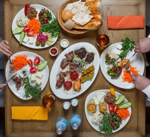 Jantar em pratos brancos contendo carne e legumes,