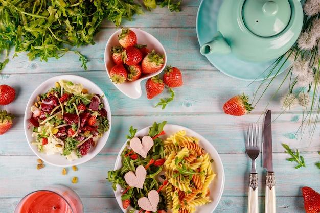 Jantar festivo de dia dos namorados com massas coloridas, salada de rúcula e morango na mesa de madeira branca