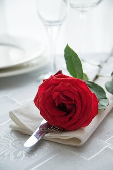 Jantar festivo ou romântico com rosa vermelha.