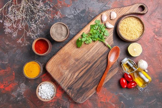 Jantar fundo tábua de cortar massas crus, limão, verduras, azeite, colher e temperos diferentes na mesa escura