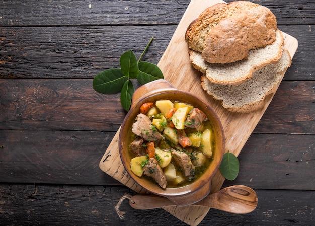 Jantar irlandês. carne cozida com batatas, cenouras e pão de soda na tabela de madeira, vista superior, espaço da cópia. comida caseira de inverno - cozida lentamente