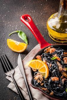 Jantar italiano moderno, comida mediterrânea, macarrão espaguete com tinta de choco preto com frutos do mar