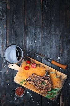 Jantar na mesa, suculento bife grelhado, uma taça de vinho tinto seco, lugar para texto