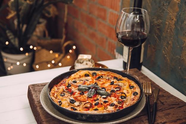 Jantar na varanda com taça de vinho tinto e pizza italiana caseira