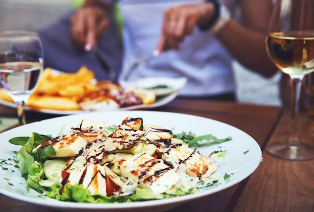 Jantar no restaurante. salada de close-up com queijo grelhado. pessoas comendo no fundo