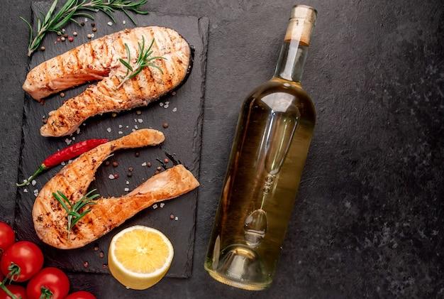 Jantar para dois bifes de salmão grelhados, garrafa de vinho e taças na mesa de pedra