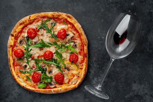Jantar para dois. deliciosa pizza italiana com queijo mussarela, cogumelos, tomate, pimentão, cebola e uma garrafa de vinho com copos.