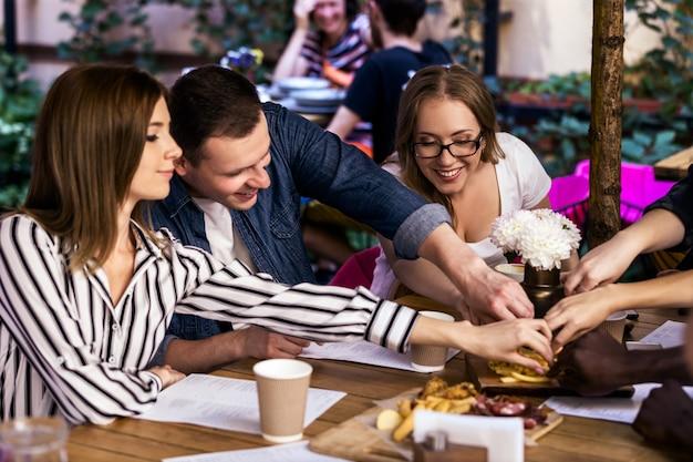 Jantar pós-trabalho com colegas na cafeteria local tranquila, com deliciosos lanches