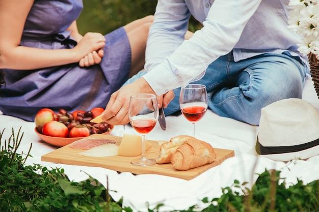 Jantar romântico ao ar livre com uvas de vinho tinto e queijo na tábua de madeira