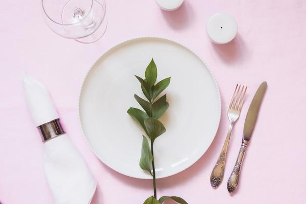 Jantar romântico. cenário de mesa elegância com planta na toalha de linho rosa.